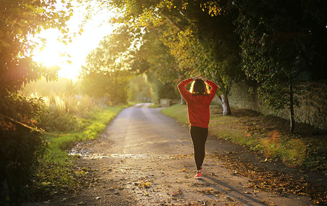 Woman walking down a country road with the evening sun shining a beautiful peaceful life.