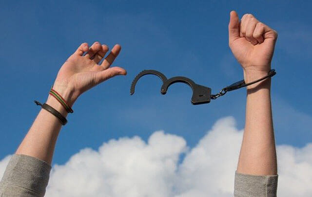 Arms in the air with blue sky breaking the chains of addiction and living sobriety for 30 days