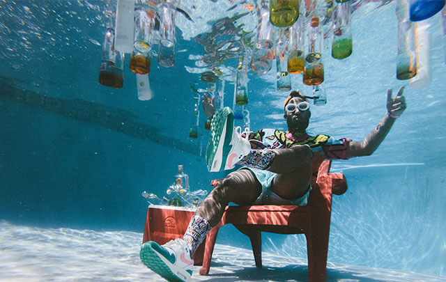 Hip man under water sitting in chair reaching for alcohol bottles floating. He is trying to stay sober but alcohol temptation is all around.
