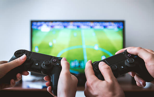 Man and woman playing soccer video game keeping busy instead of drinking.