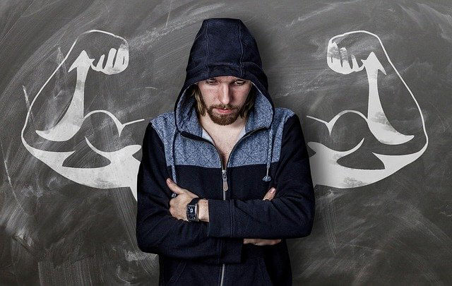 Sober man standing in front of chaulkboard with muscle arms drawn on it