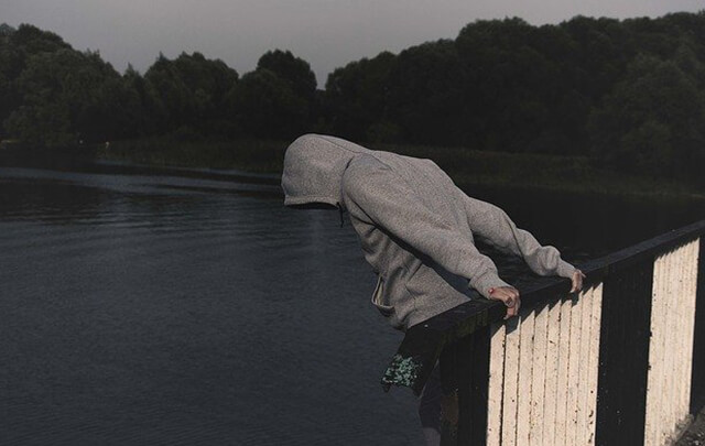 Alcoholic leaning over the edge of a bridge contemplating jumping.