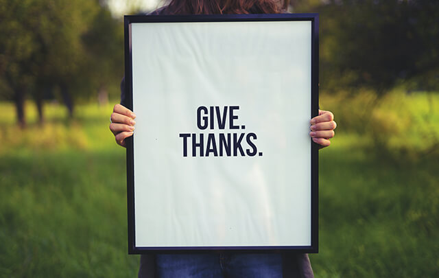 Woman standing in field holding sign that says Give Thanks.