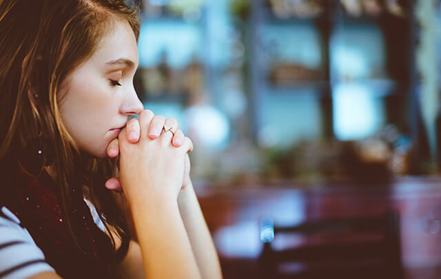 Young woman sitting at the table with her eyes closed and hands are folded.  She is resting her mouth on her hands while sitting at a table meditating.