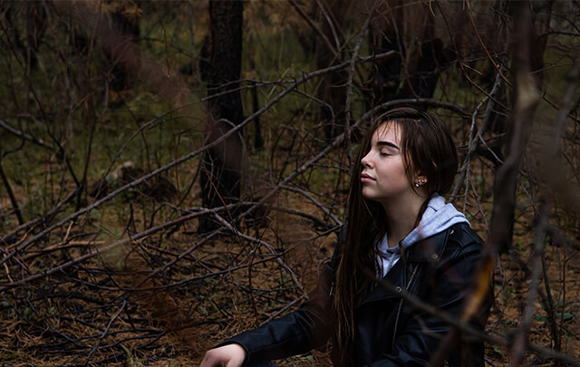 Woman sitting in woods meditating