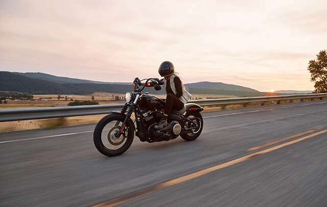 Woman right motorcycle down highway with beautiful mountains and sunset the background.