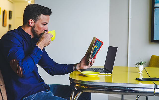 Man sitting at yellow table in sober living house, sipping out of a yellow mug reading a book.