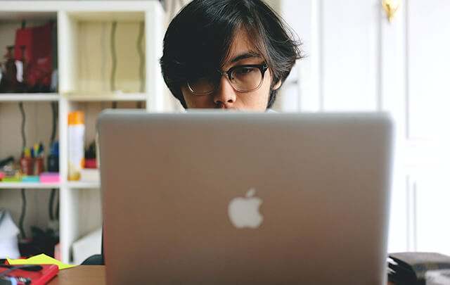 Asian man sitting behind Apple Laptop only his nose and above are visible.