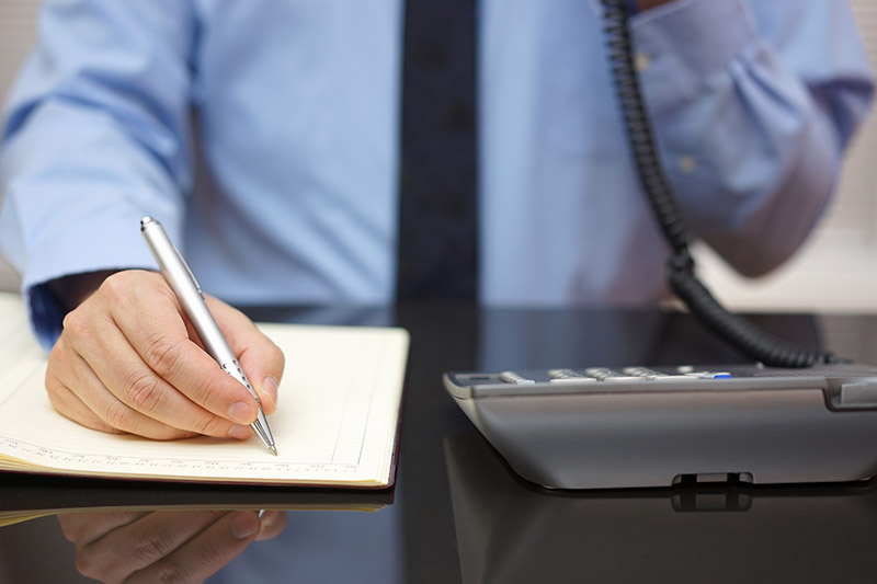 Businessman using telephone while writing in notebook at desk