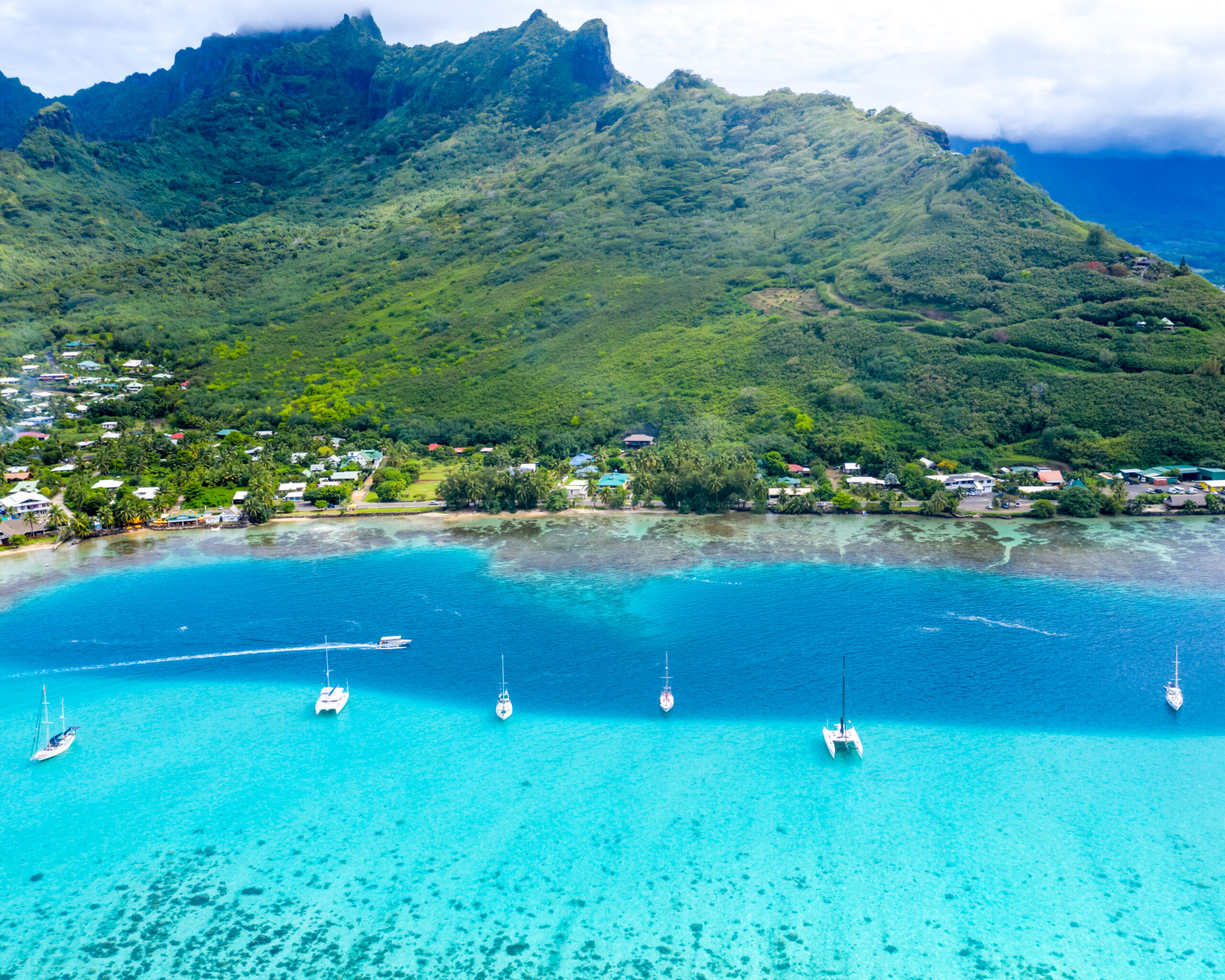 best drone shots by Ashley. Double split shot from the Island of Moorea, French Polynesia. Volcanic mountains covered in green on teh top, then dark blue waters and brigh aqua water. On the line where the color of the water splits there are sail boats anchored.