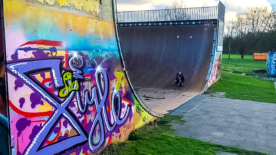 girl on her trip around Southern Germany sliding down a half pipe in Bonn Germany that has grafitti on the sides. Bright purple, pink, green, yellow.