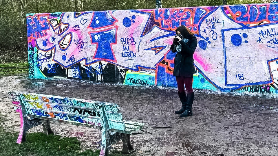 Girl on her trip around Southern Germany taking a photograph of a grafittied bench in Bonn Germany