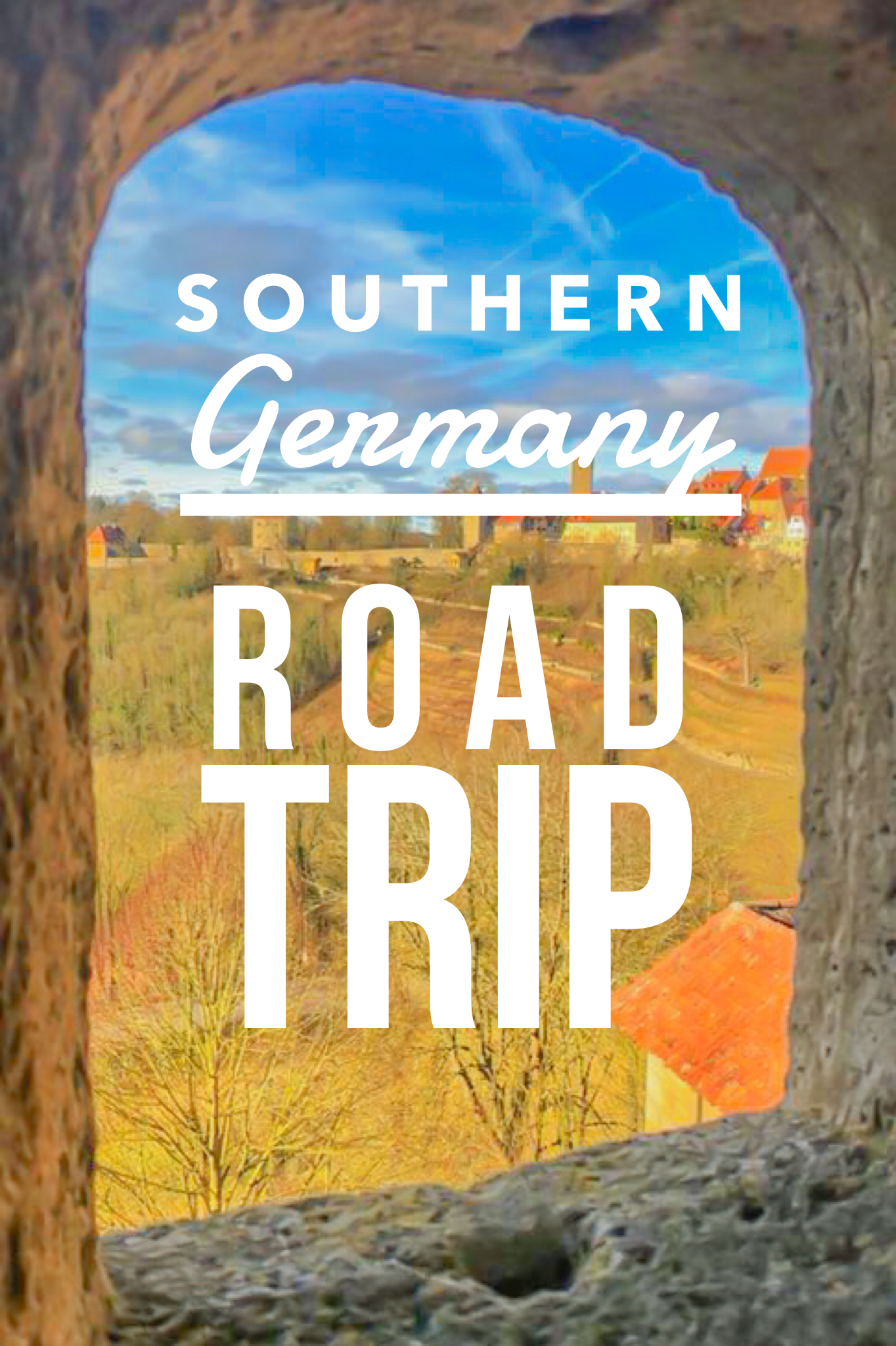 Text says, road trip of southern Germany and the photo is looking out a peep hole from a city wall of Rothenburg ob der Tauber, Germany
