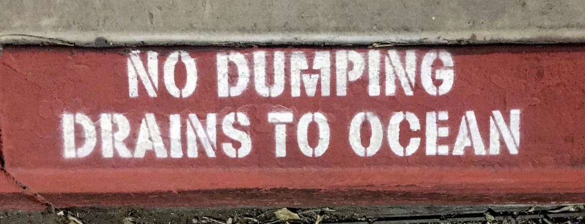 photo of a curb in california that is painted red and says, No dumping drains to ocean. From eco friendly post on ashmonster.com