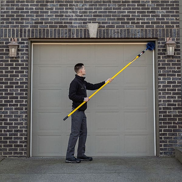 Aspen Pest Control technician cleaning the corners of a garage door for webs