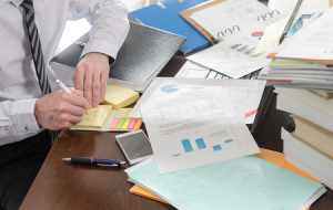 42625038 - businessman working at a untidy and cluttered desk