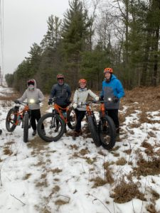 Family poses for a Winter Fat Bike picture mid guided tour in Cable, WI