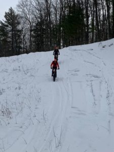 2 Brothers riding fat bikes down snow groomed trail in Winter.