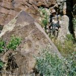 """This Large triangular stone is a common feature at Kuskurza. In fact it is the predominant monument used throughout the site by far. Only being out matched by the """"3 steps"""" symbology itself. So much so that you could call these """"The People of the Triangle"""". Which should not surprise as they are claimed to have survived in the """"underworld"""" subterranean realm of the """"second step"""" before emerging to the surface here the """"3rd step"""". The triangle being strongest supporting shape. You can see me upper right examining it for scale. This is not the largest example by far, but only moderate by comparison at around 20 tons or 40,000lbs."""