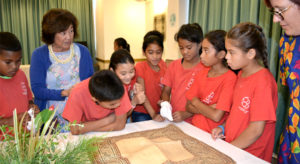 Majuro Cooperative School students pay close attention to a jaki-ed that was made over 100 years ago and was on loan from the Bishop Museum in Honolulu for last week's jaki-ed event in Majuro. MaryLou Foley, at left, talks about the mats to the students. Photo: Aileen Sefeti.