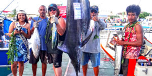 "Team Dragon, captained by Rudy Aliven (standing next to marlin, right), ""caught five"" fish species to win the Catch Five carry over prize from a previous tournament during Friday's first day of fishing in the 36th annual Marshalls Billfish Club July tournament. Photo: Hilary Hosia."