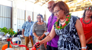 President Hilda Heine cuts the ribbon to the new can and bottle recycling equipment at Majuro Atoll Waste Company's recycling center as MAWC Manager Jorelik Tibon and other VIPs look on. Photo: Hilary Hosia.