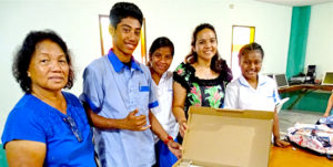 Assumption Principal Biram Stege, left, and daughter and fundraiser Tina Stege, second from right, with Assumption High School students receiving the new laptops at the school in Majuro. Photo: Kelly Lorennij.