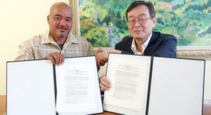 Arno Mayor Bernard Chong Gum and Japan Ambassador Norio Saito show the grant agreement after the signing ceremony last week.