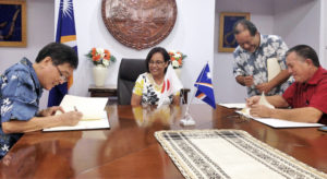 Japan Ambassador Norio Saito, left, and RMI Foreign Minister John Silk, right, sign two grant agreements while President Hilda Heine and Foreign Secretary Bruce Kijiner look on.