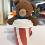 Childhood stuffed bear drinking a large coffee in Australia
