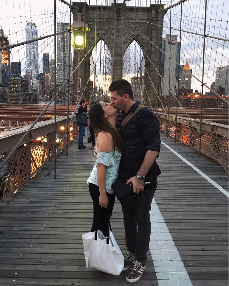 Reunited couple kissing on the Brooklyn Bridge at night in New York