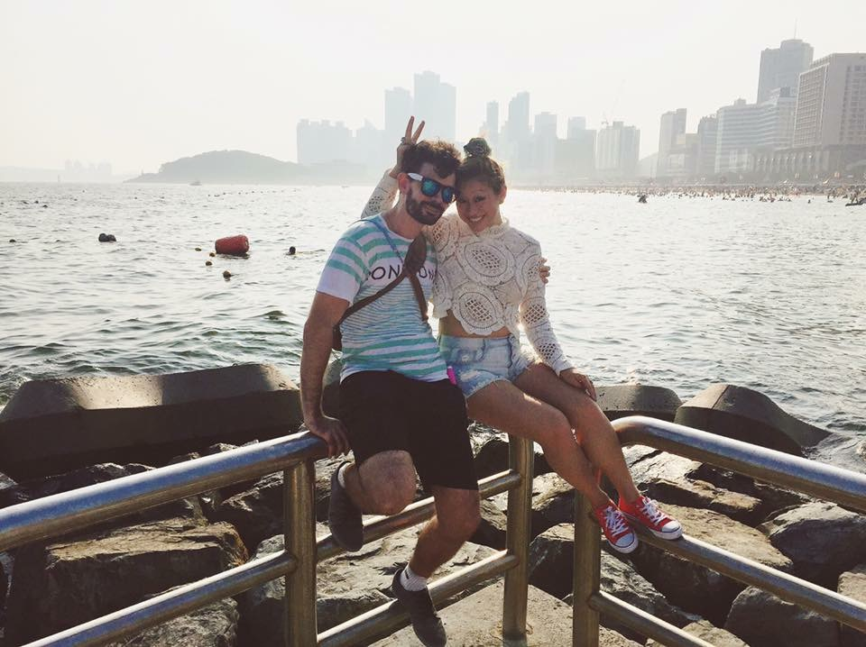 Taiwanese American and Australia young couple in Busan South Korea's Haeundae Beach taking a break and enjoying the water and skyline