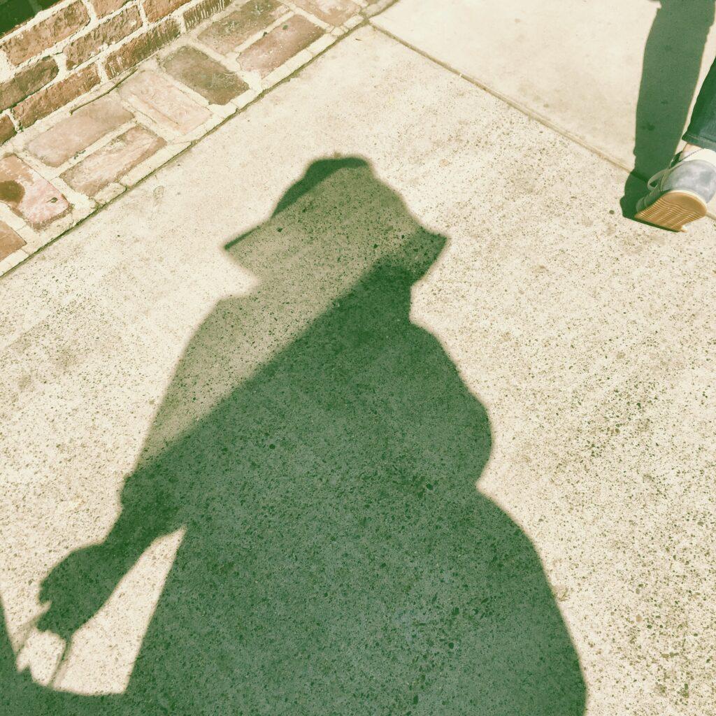 Shadow in the sunlight wearing a floppy hat
