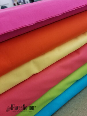 Stack of bright Kona Solid fabric