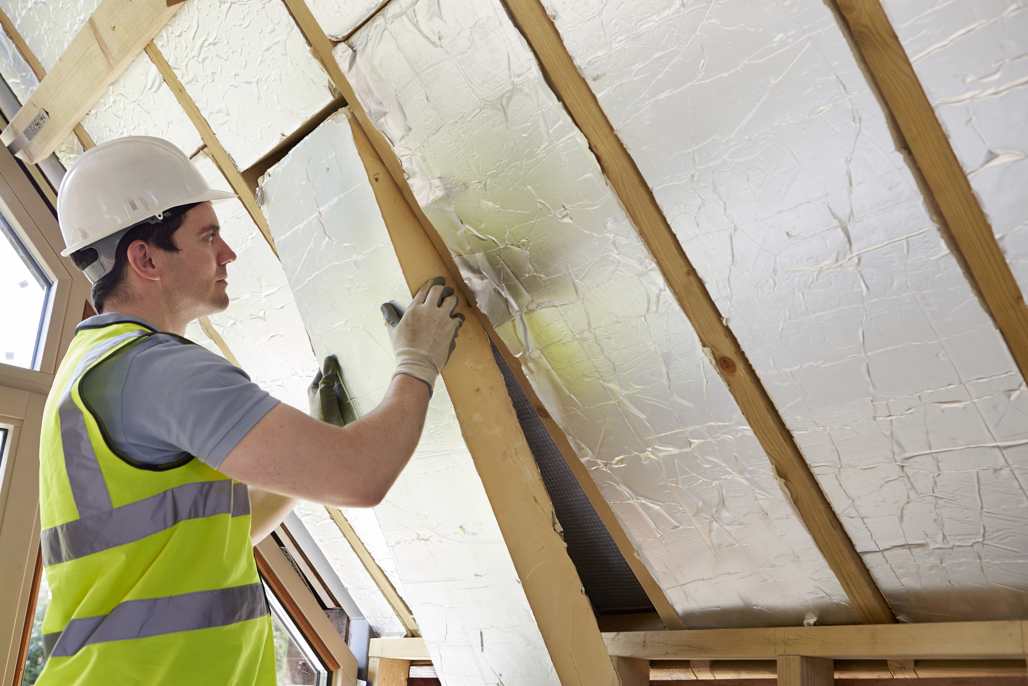 Man laying insulation in the roof to increase R-value