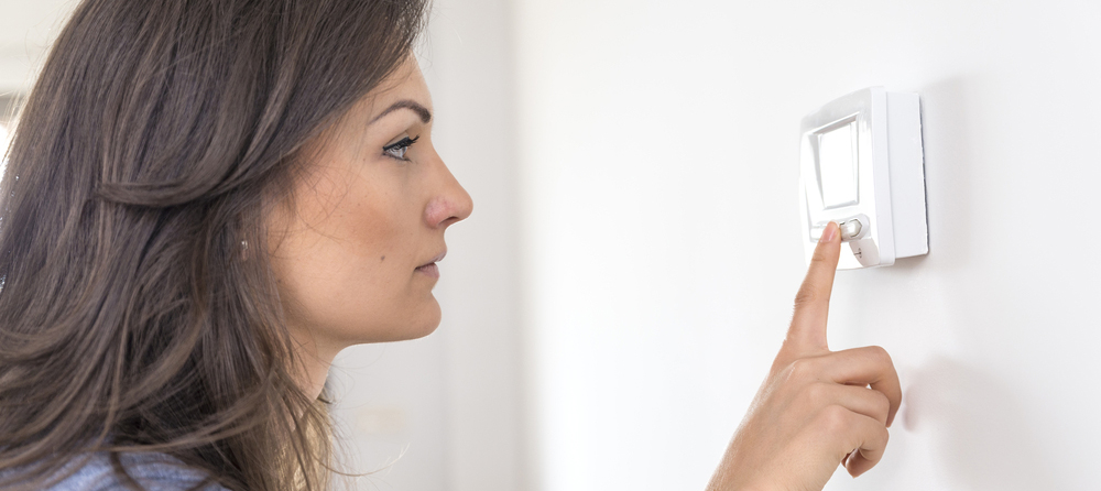 Woman checking ac thermostat