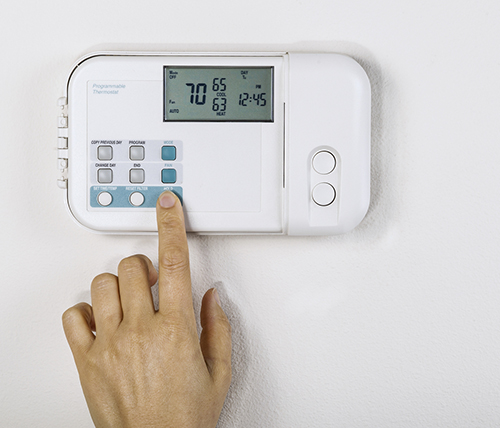 Person changing thermostat temperature