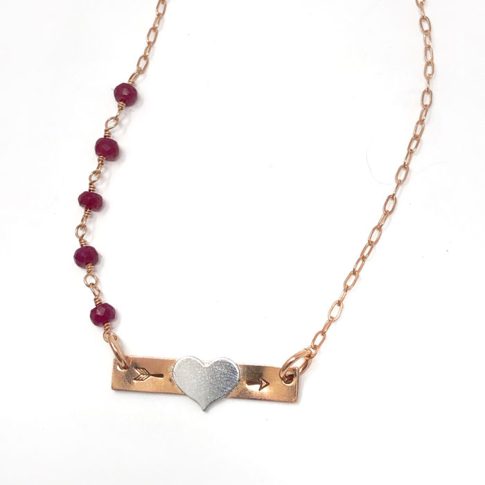 Rose gold bar necklace with heart initial and gemstones.
