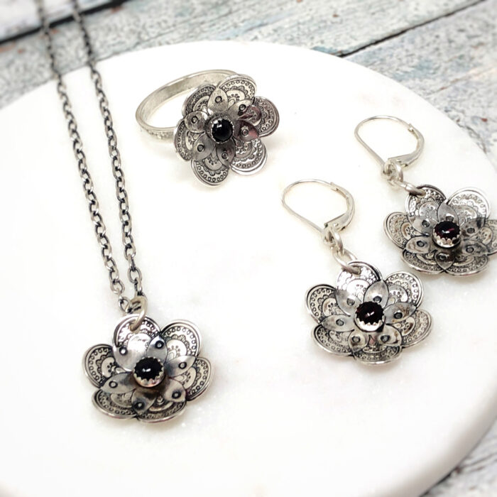 Flower collection in silver with garnet stone; earrings, necklace and ring