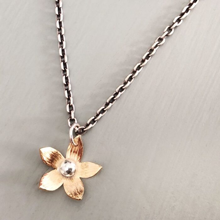 Tiny brass flower with sterling silver chain