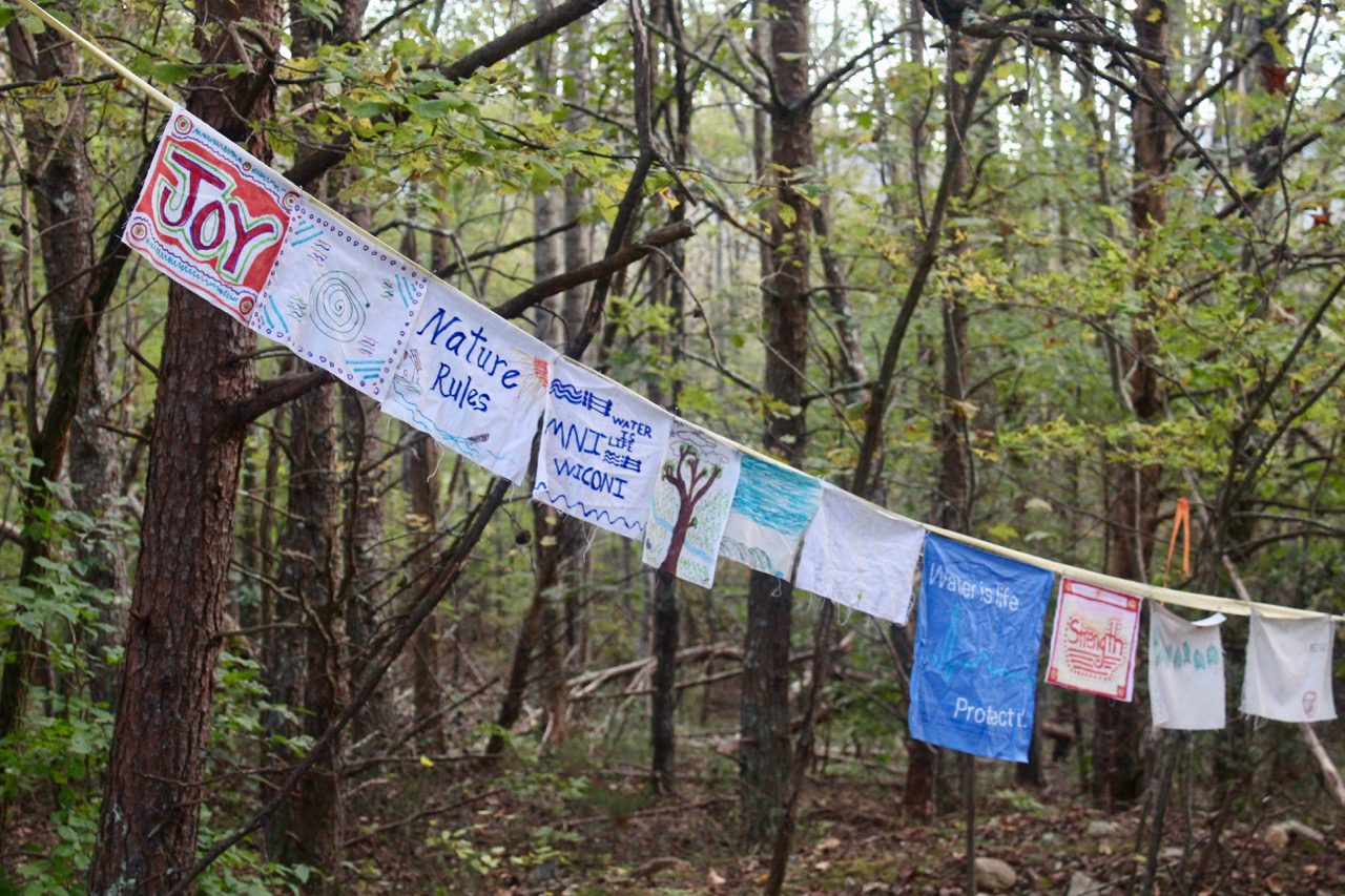 Prayer flags attached on a string, tied to trees at the campsite along the proposed pipeline route.