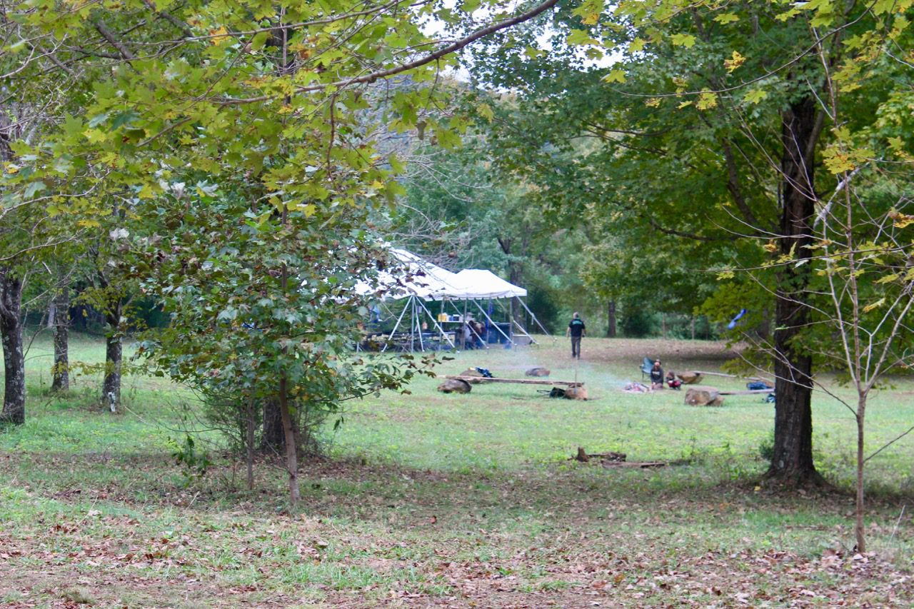 The main campsite at Spruce Creek, a large tent surrounded by benches, grills and trees.