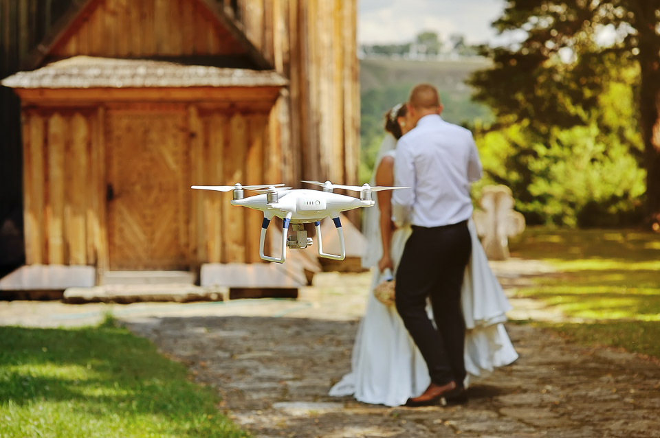 drone filming a wedding couple by the oold wooden church