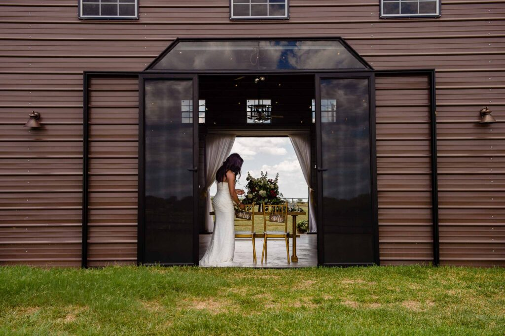 a bride at the sweetheart table at the cirlcle j ranch, a wedding venue in von ormy, texas