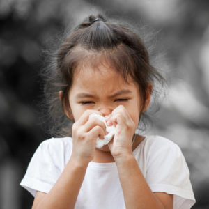 Sick little asian girl wiping or cleaning nose with tissue on her hand