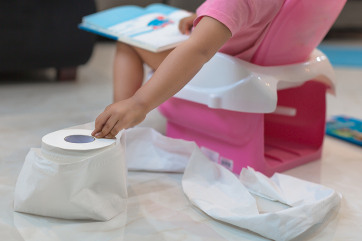 Child using the potty by herself while reading a book, reaches for a sheet of toilet paper