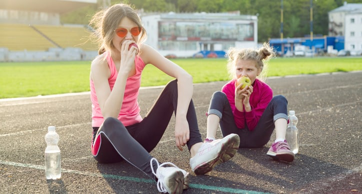 Healthy eating and healthy lifestyle in children, girl teenager and girl 7 years after playing sports sitting in the stadium drinking water and eating apples