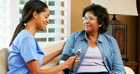 caretaker taking blood pressure of old lady
