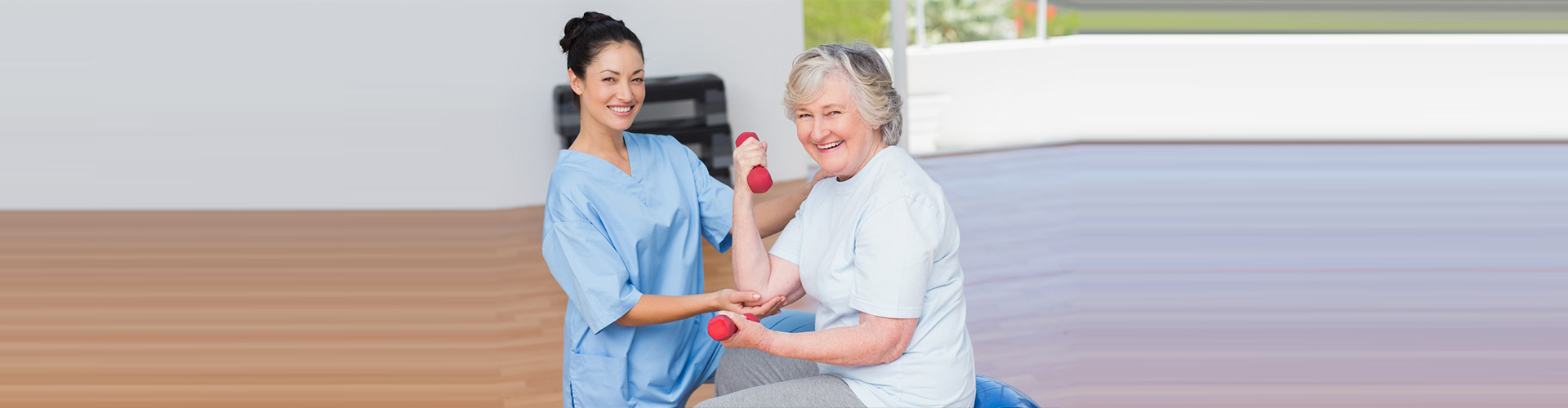 caretaker helping old woman with dumbells