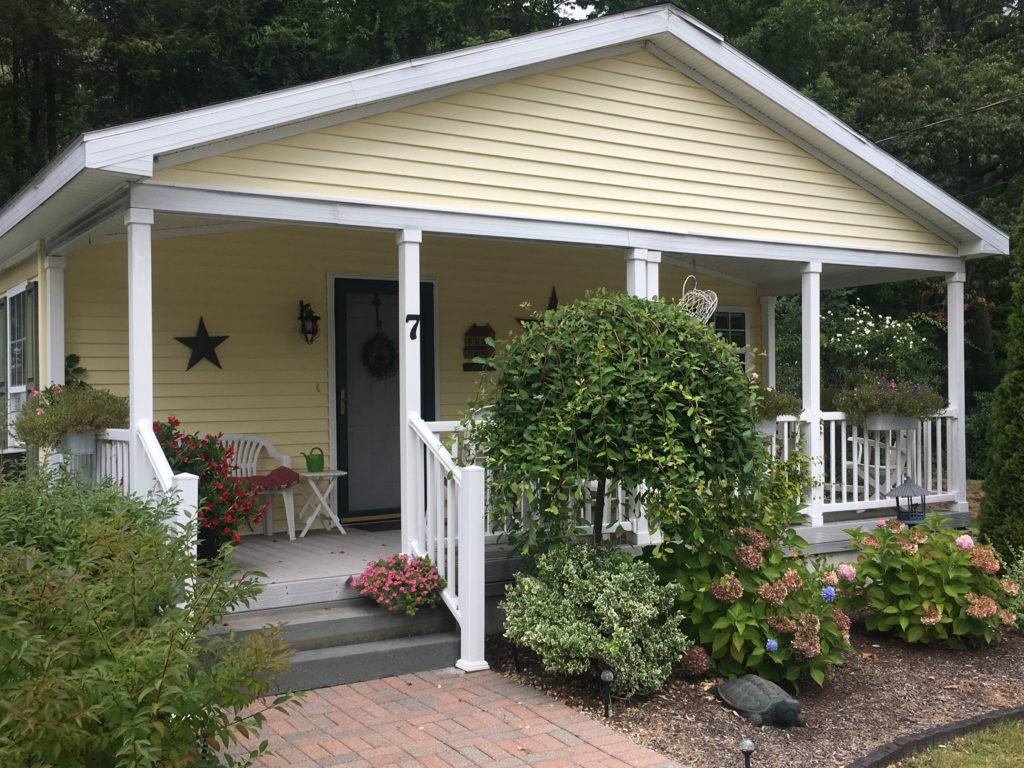 Bigelow Village Home - yellow and white siding with front porch and beautiful plantings